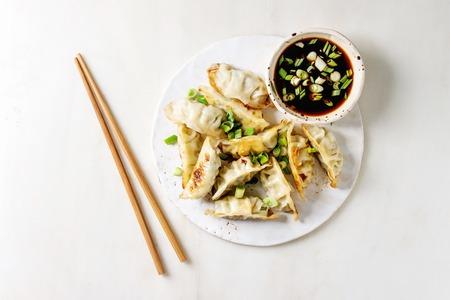 Gebratene asiatische Knödel Gyozas Potstickers in weißer Keramikplatte serviert mit Stäbchen und Schüssel mit Soja-Zwiebel-Sauce auf weißem Marmorhintergrund. Flache Lage, Raum. Asiatisches Abendessen Standard-Bild