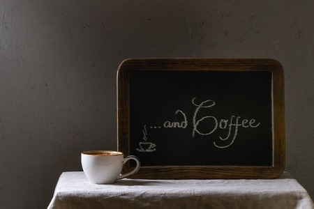 Cup of espresso coffee standing on linen table cloth. Vintage chalkboard with lettering behind