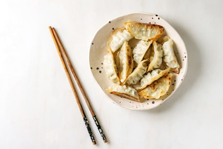 Fried asian dumplings Gyozas potstickers in white ceramic plate served with chopsticks and soy spring onion sauce over white marble background. Flat lay, space. Asian dinner Stockfoto
