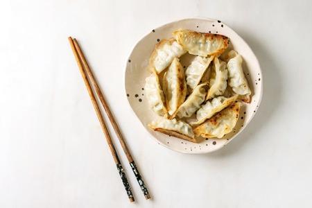 Gebratene asiatische Knödel Gyozas Potstickers in weißer Keramikplatte serviert mit Stäbchen und Soja-Frühlingszwiebelsoße auf weißem Marmorhintergrund. Flache Lage, Raum. Asiatisches Abendessen Standard-Bild