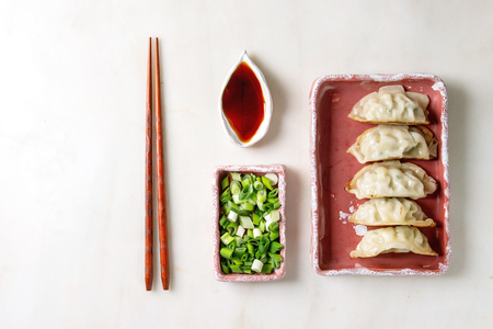 Fried asian dumplings Gyozas potstickers in pink square ceramic plate served with chopsticks, bowl of soy sauce, chopped spring onion over white marble background. Flat lay, space. Asian dinner