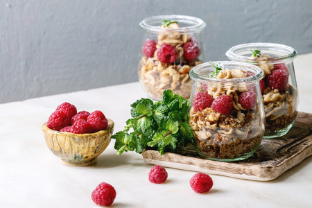 Layered dessert in jars. Biscuit, coffee cream, nuts, raspberries, fresh mint. Served on ceramic tray with berries and greens over white marble table.