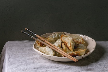 Fried asian dumplings Gyozas potstickers in white ceramic plate served with chopsticks over linen table cloth. Asian dinner