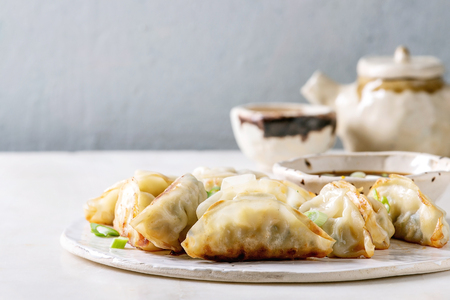 Fried asian dumplings Gyozas potstickers in white ceramic plate served with bowl of soy onion sauce, teapot over white marble table. Grey wall at background. Asian dinner