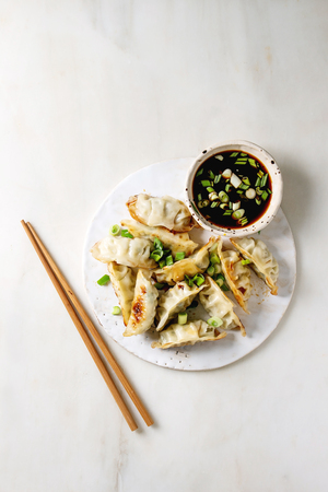 Fried asian dumplings Gyozas potstickers in white ceramic plate served with chopsticks and bowl of soy onion sauce over white marble background. Flat lay, space. Asian dinner Stockfoto