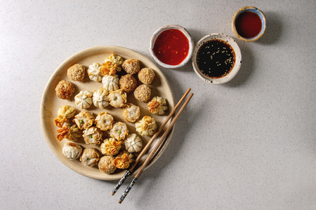 Dim sum Gyozas asian fried dumplings party set with variety of sauces served in ceramic plates and bowls with chopsticks over grey spotted background. Flat lay, space