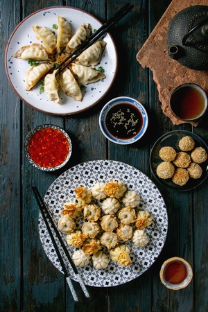Dim sum Gyozas asian fried dumplings party set with variety of sauces served in ceramic plates and bowls with chopsticks, tea cups and teapot over dark blue wooden background. Flat lay, space