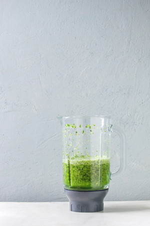 Green spinach kale apple smoothie in glass blender on white marble table. Healthy organic eating. Stock Photo