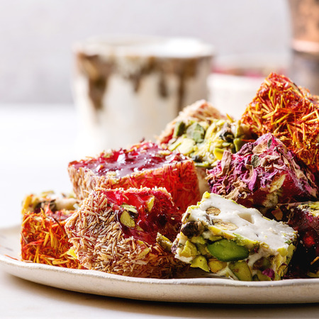 Variedad de postre turco tradicional Delicia turca de diferentes gustos y colores pétalos de rosa y pistachos en placa de cerámica con jezve de café y jarra de leche en la mesa de mármol blanco. De cerca. Imagen cuadrada Foto de archivo