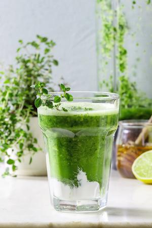 Groene spinazie boerenkool appel honing smoothie met yoghurt en tijm in glas op witte marmeren tafel met blender en ingrediënten hierboven. Gezond biologisch eten. Detailopname