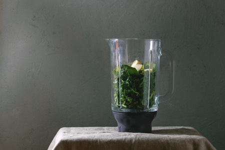 Ingredients for green spinach kale apple smoothie in glass blender on linen table cloth. Healthy organic eating.