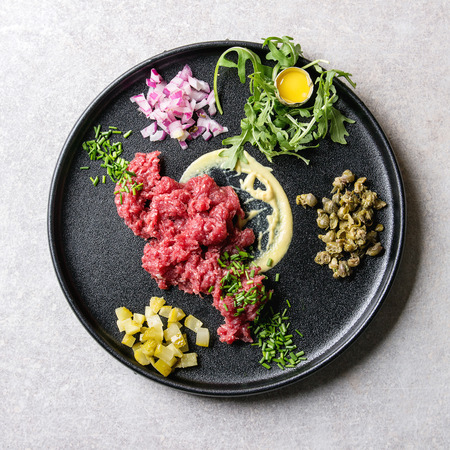 Beef tartare with quail egg in shell, cutting pickled cucumbers, capers, red onion, chives, arugula salad served in black ceramic plate over grey background. Flat lay, space. Square image