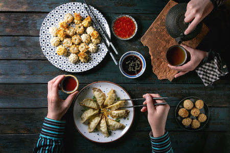 Family or friends dinner with Dim sum Gyozas asian fried dumplings set, variety of sauces served in ceramic plates with chopsticks, tea cups and teapot. Dark blue wooden background. Flat lay, space