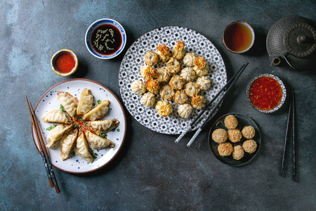 Dim sum Gyozas asian fried dumplings party set with variety of sauces served in ceramic plates and bowls with chopsticks, tea cups and teapot over dark blue texture background. Flat lay, space Stock Photo