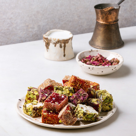 Variety of traditional turkish dessert turkish delight different taste and colors rose petals and pistachio nuts on ceramic plate with coffee jezve and milk jug on white marble table. Square image