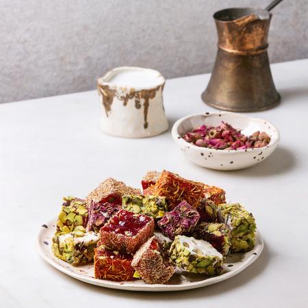 Vielzahl von traditionellen türkischen Desserts türkische Freude mit unterschiedlichem Geschmack und Farben Rosenblüten und Pistazien auf Keramikplatte mit Kaffee-Jezve und Milchkanne auf weißem Marmortisch. Quadratisches Bild Standard-Bild
