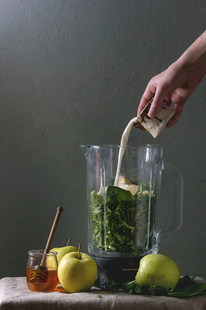 Ingredients for green spinach kale apple honey smoothie in glass blender on linen table cloth with ingredients above. Young man pouring milk. Healthy organic eating.