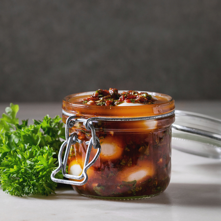 Opened Jar with homemade pickled marinated quail eggs in tomato and olive oil sauce with anchovies and fresh parsley on white marble kitchen table. Copy space. Square image Stock Photo - 121459974