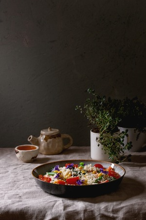 Couscous salad with parboiled vegetables baby carrots, green beans, sweet corn, spinach in ceramic plate with tomatoes, sesame and edible flowers, tea cup and teapot on linen table cloth. Vegan food. 스톡 콘텐츠