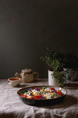 Salade de couscous aux légumes étuvés carottes miniatures, haricots verts, maïs sucré, épinards dans une assiette en céramique avec tomates, sésame et fleurs comestibles, tasse à thé et théière sur nappe en lin. Nourriture végétalienne.