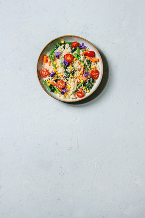Couscous with parboiled vegetables baby carrots, green beans, sweet corn, spinach in ceramic plate with tomatoes, sesame and edible flowers. Vegan food. Grey concrete background. Flat lay, space