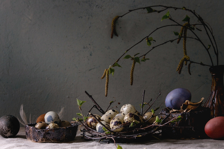 Variety of colored and quail Easter eggs in birds nest with young blooming birch branches in ceramic vase standing on grey linen table cloth with wall at background. Easter holidays decorations.