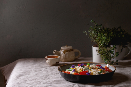 Couscous salad with parboiled vegetables baby carrots, green beans, sweet corn, spinach in ceramic plate with tomatoes, sesame and edible flowers, tea cup and teapot on linen table cloth. Vegan food. Zdjęcie Seryjne