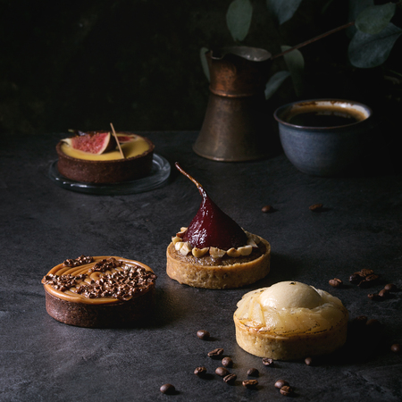Variety of sweet tartlets with chocolate, caramel, pears, figs with cup of coffee and coffee beans around on black texture table. Square image