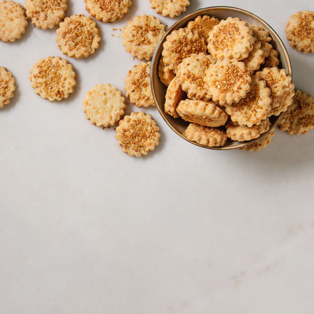 Homemade snack shortbread cheese sesame cookies in bowl over white marble background. Flat lay, space. Square image
