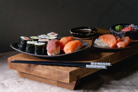 Sushi Set nigiri and sushi rolls on japanese wooden serving board with soy sauce, chopsticks on grey linen table cloth. Japan menu