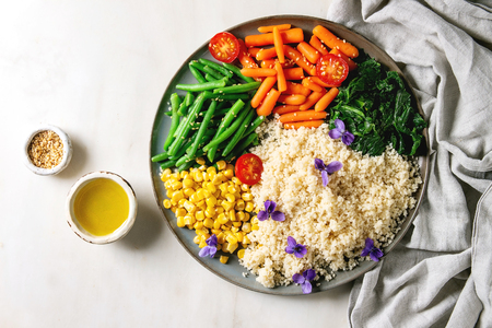 Couscous with parboiled vegetables baby carrots, green beans, sweet corn, spinach served in ceramic plate with tomatoes, sesame and edible flowers. Vegan food. White marble background. Flat lay, space