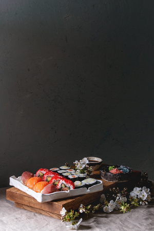 Sushi Set nigiri and sushi rolls on japanese wooden serving board with soy sauce, chopsticks, spring blossom cherry branches on grey linen table cloth. Japan menu Stock Photo - 121460375
