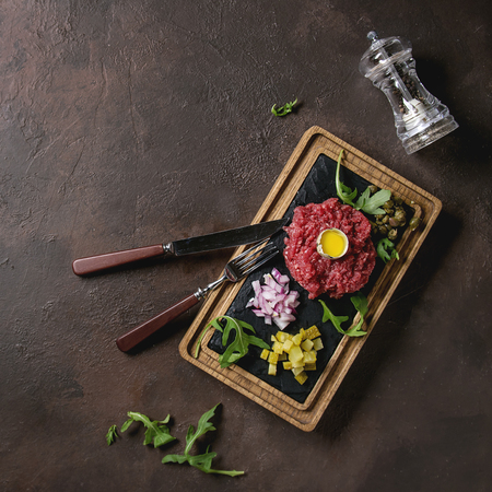 Beef tartare with quail egg in shell, cutting pickled cucumbers, capers, red onion, chives, arugula served on wooden black slate board with cutlery on dark texture background. Flat lay, space. Square image