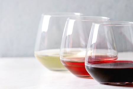 Variety of wine. Red, rose and white wine in old fashion glasses in row on white marble table. Copy space Archivio Fotografico