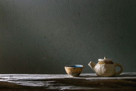 Craft handmade ceramic teapot and cup for tea ceremony standing on old wooden shelf in dark room.