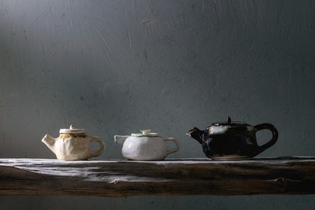 Variety of craft handmade ceramic teapots for tea ceremony standing on old wooden shelf in dark room.