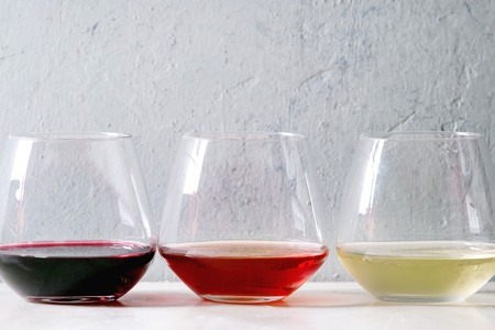 Variety of wine. Red, rose and white wine in old fashion glasses in row on white marble table. Copy space Фото со стока