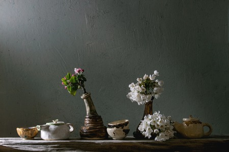 Variety of craft handmade ceramic teapots and cups for tea ceremony standing with spring blossom branches in vase on old wooden shelf in dark room.