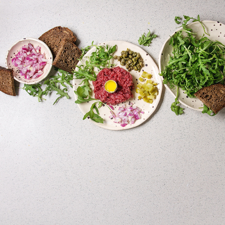 Beef tartare with quail egg in shell, bread, cutting pickled cucumbers, capers, red onion, arugula salad served in spotted ceramic plates on grey background. Flat lay, space. Square image Stock fotó