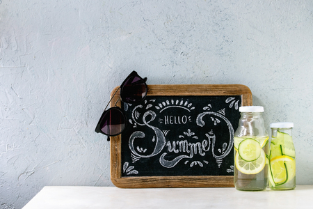 Summer theme. Chalk lettering Hello summer on vintage chalkboard, sunglasses and two glass bottles with sassy lemon and cucumber water on white marble table with concrete wall at background. Foto de archivo - 121460597