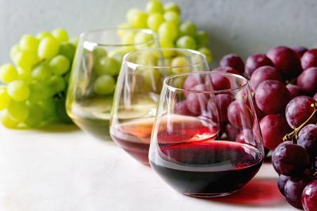 Varietà di vino. Vino rosso, rosato e bianco in bicchieri vecchio stile con grappoli d'uva su tavolo in marmo bianco Archivio Fotografico