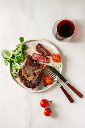 Grilled roasted sliced medium rare beef steak served in ceramic plate with green field salad, cherry tomatoes, cutlery, pepper, glass of red wine over white marble background. Flat lay, space