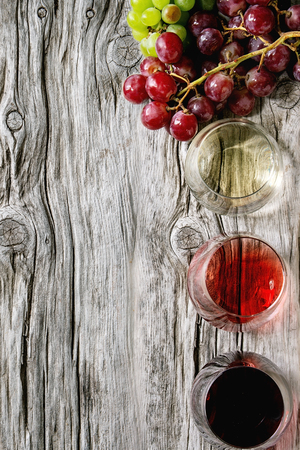 Variety of wine. Red, rose and white wine in old fashion glasses with bunches of grapes over old wooden background. Flat lay, space Archivio Fotografico