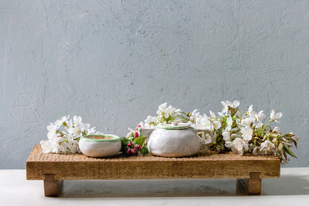 Craft handmade ceramic teapot and cup with hot tea decorated by spring blossom cherry branches on japanese style wooden serving tray on white marble table.