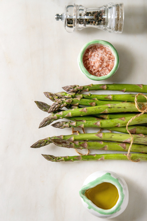 Bundle of raw organic green asparagus with cooking ingredients pink sea salt, black pepper and olive oil over white marble background. Flat lay, space Stock Photo