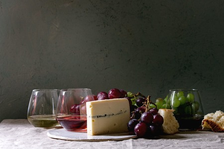 Variety of wine. Red, rose and white wine in old fashion glasses with bunches of grapes, blue cheese on ceramic board and bread on grey linen table cloth. Dark still life. Copy space