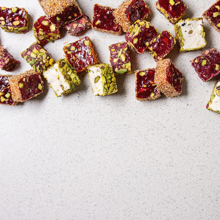 Variedad de postre turco tradicional Delicia turca de diferentes sabores y colores con pétalos de rosa y pistachos sobre fondo gris manchado. Endecha plana, copia espacio de copia. Imagen cuadrada