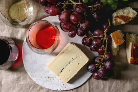 Variety of wine. Red, rose and white wine in old fashion glasses with bunches of grapes, blue cheese on ceramic board and bread on grey linen cloth. Dark still life. Flat lay, space Stock Photo - 122795884