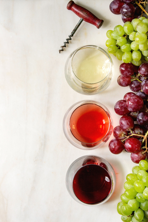 Variety of wine. Red, rose and white wine in old fashion glasses with bunches of grapes and vintage corkscrew. White marble background. Flat lay, space