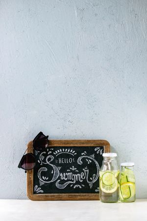 Summer theme. Chalk lettering Hello summer on vintage chalkboard, sunglasses and two glass bottles with sassy lemon and cucumber water on white marble table with concrete wall at background. Foto de archivo - 122795900